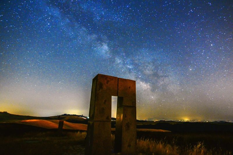 Old monument on field against starry sky