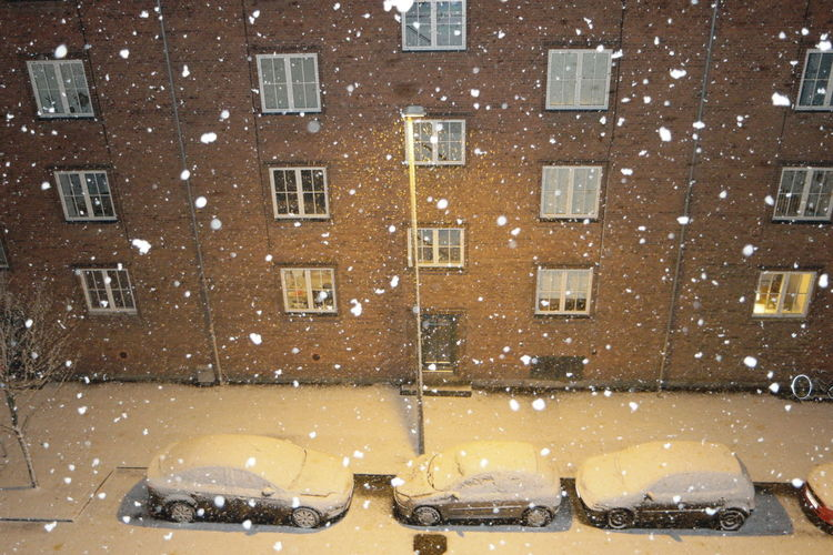 Cars parked in front of a residential building in winter