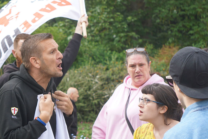 EDL protester is confronted by pro-migrant protestor at Friendship Picnic event to welcome refugees Anger Anti-Fascist Anti-migrant Casual Clothing Confrontation Day Disagreements Focus On Foreground Front View Headshot Lifestyles Mid Adult Men Person Portrait Protest The Photojournalist - 2016 EyeEm Awards