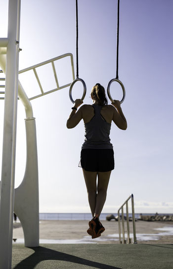 Full length rear view of woman hanging from gymnastic rings against sky