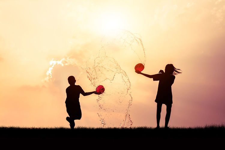 Full length silhouette friends splashing water on each other while standing against sky during sunset