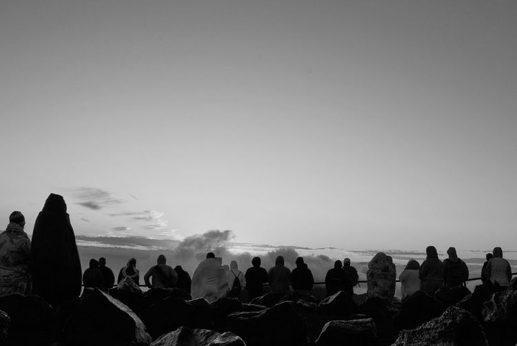 Rear view of people at haleakala crater against sky