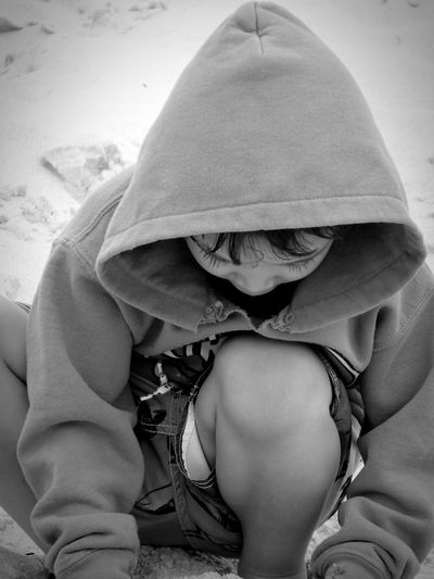 Boy In Hooded Shirt Crouching On Footpath