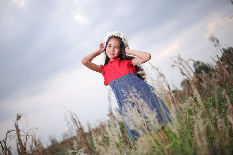 Portrait of smiling cute girl standing amidst plants on field during sunset