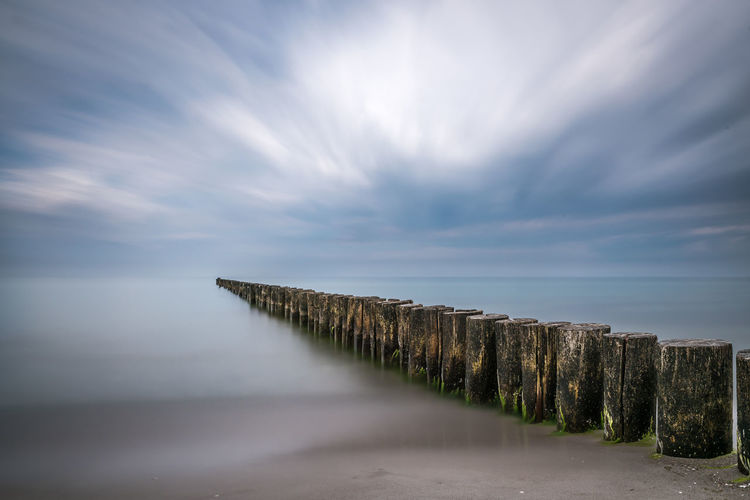 Wooden groyne in lake against cloudy sky