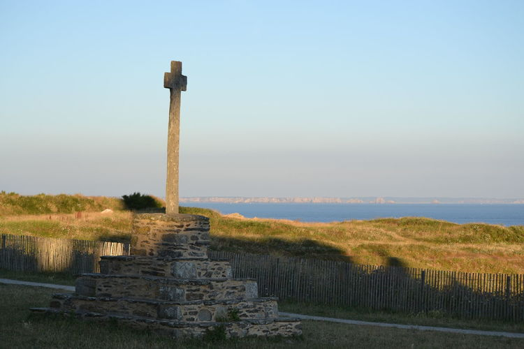 Stone cross on land against sky