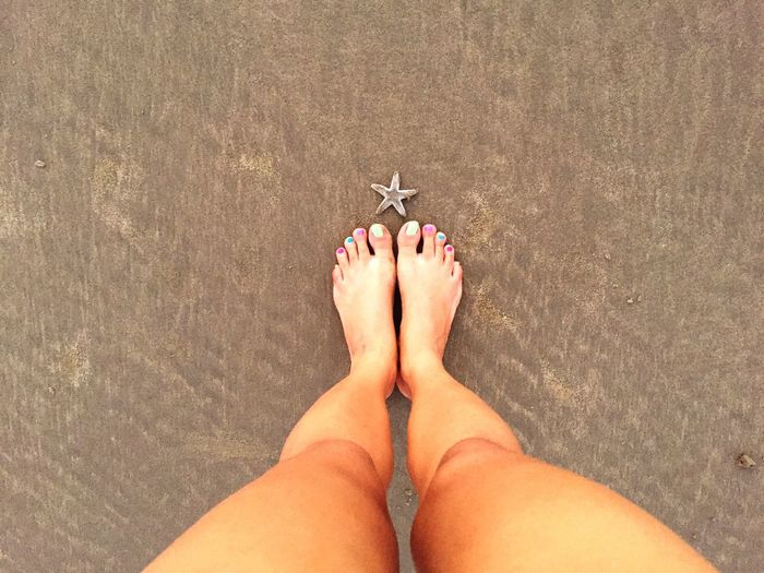 Low Section Of Woman Standing By Star Fish On Sand At Beach