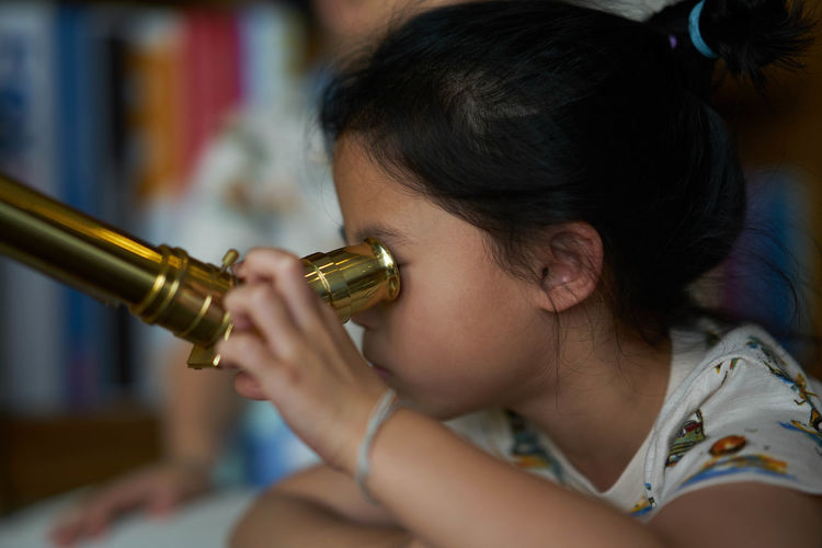 Close-up of girl looking through binoculars