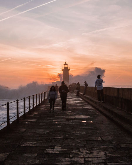 People By Lighthouse Amidst Sea Against Sky During Sunset