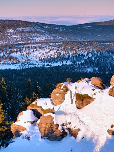 Rocky peak above inverse mist. winter weather in mountains, colorful fog. misty valley in winter