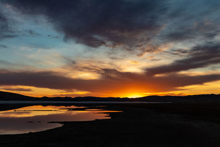 Mongolia Sunset Cloud - Sky Sky Beauty In Nature Scenics - Nature Water Tranquility Tranquil Scene Orange Color Nature No People Land Non-urban Scene Silhouette Lake Idyllic Beach Environment Outdoors The Traveler - 2019 EyeEm Awards