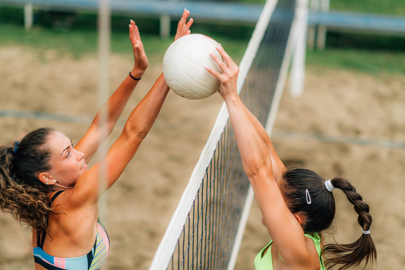 Beach volleyball female player on the net