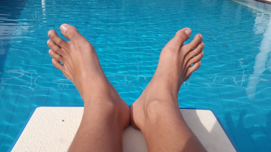 Low section of woman sitting on diving platform over swimming pool