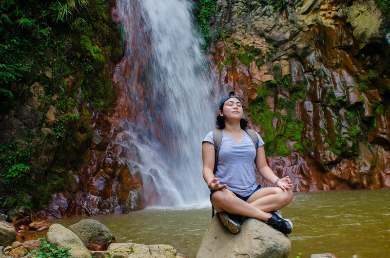 Young woman mediating while sitting on rock against waterfall in forest