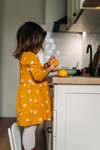 Midsection of woman with orange at home