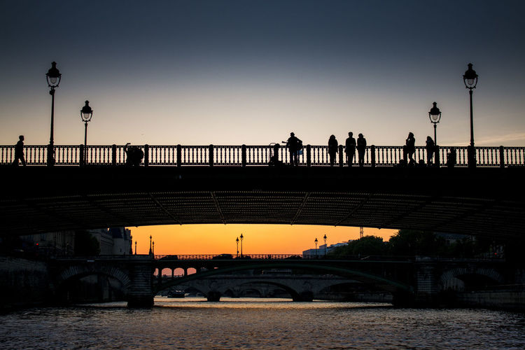 Silhouette bridge over river against sky during sunset