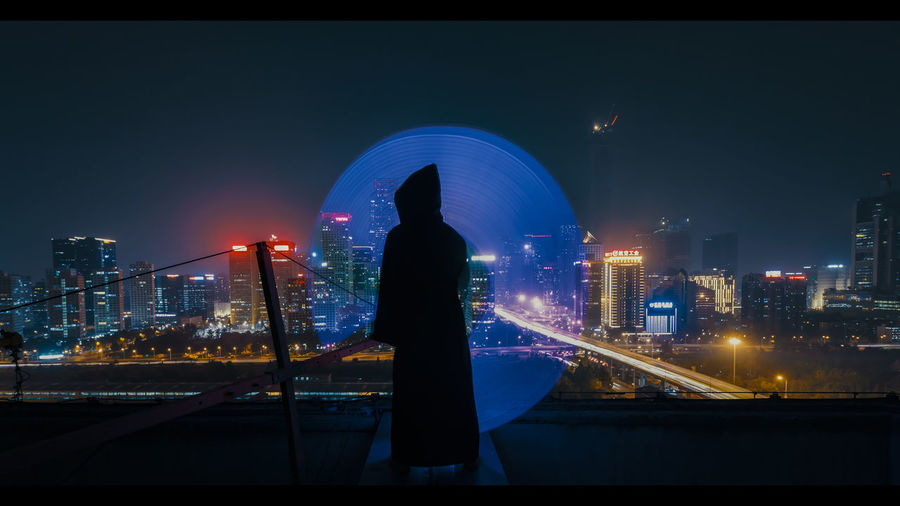 Rear view of man standing by illuminated buildings in city at night