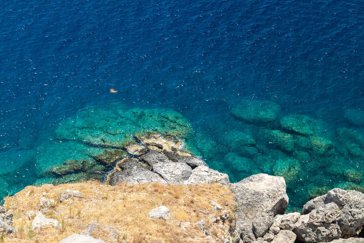 View from the acropolis on the rocky coast with blue and turquoise water in lindos on rhodes island