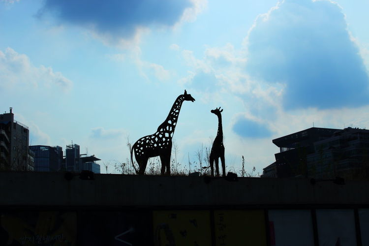 Giraffe silhouette at the top Architecture City Cloud - Sky Day No People Outdoors Sculpture Sky Statue