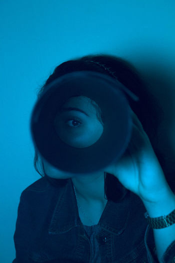 Portrait of woman against looking through circle against blue background