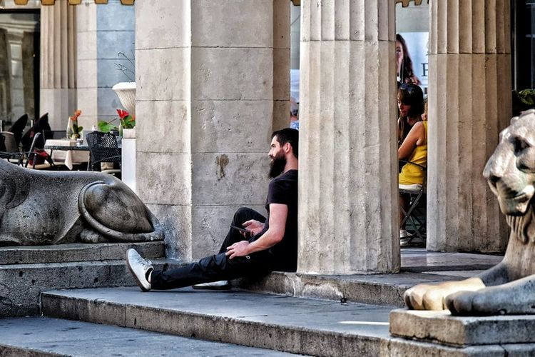People sitting on staircase in city