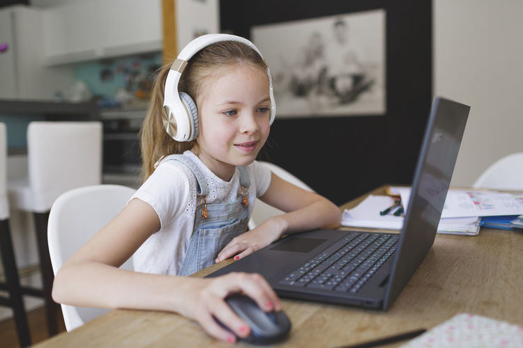Smiling girl using laptop sitting at home