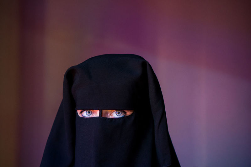 Portrait of woman wearing burka against wall