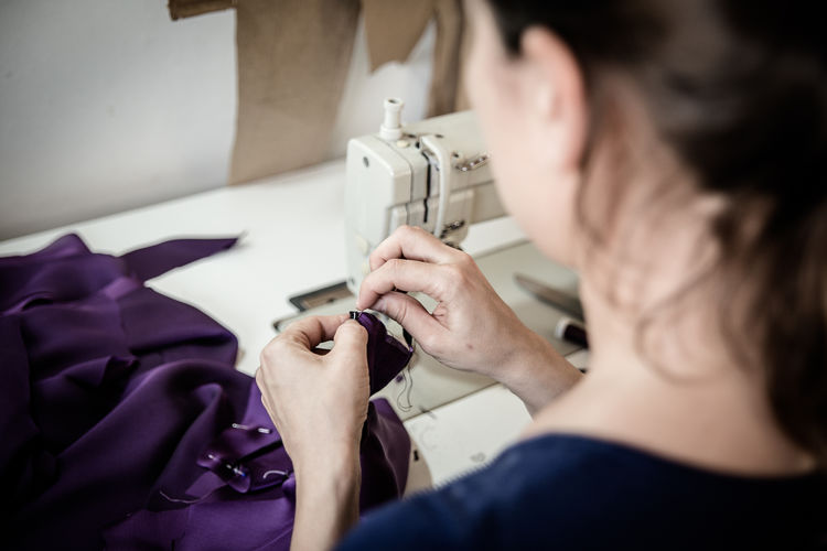 Rear View Of Woman Sewing Purple Fabric