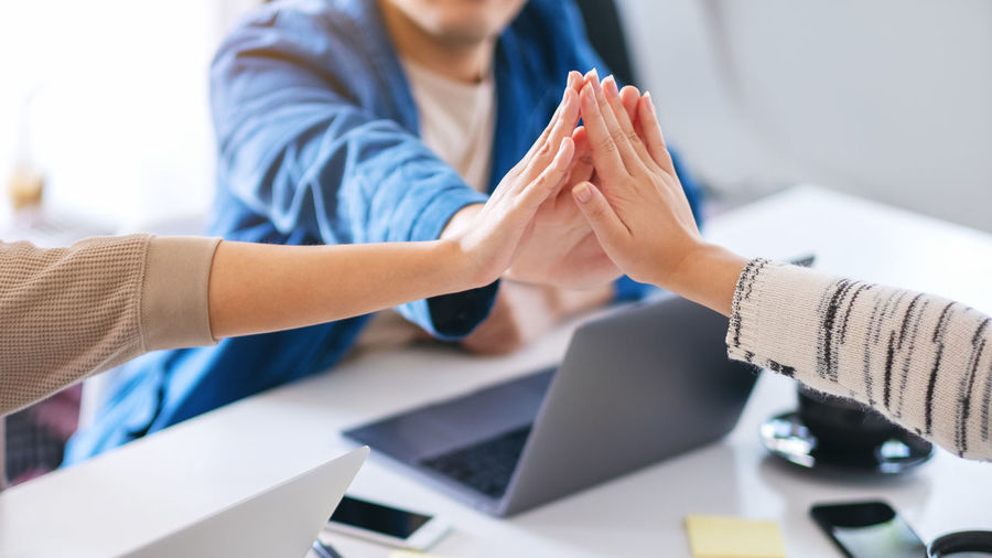 Business coworkers doing high-five in office