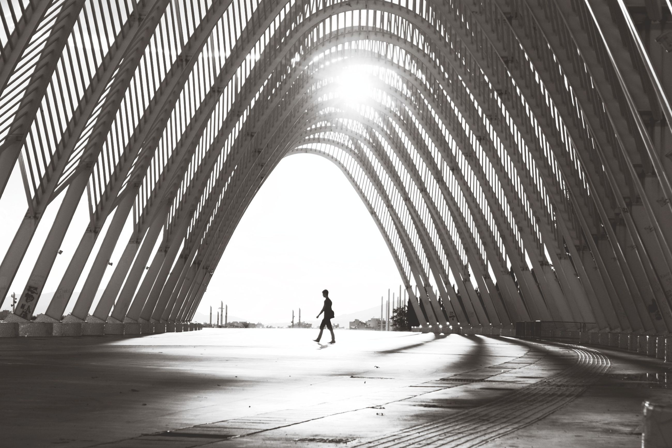 the way forward, diminishing perspective, built structure, arch, walking, architecture, incidental people, tunnel, vanishing point, connection, road, sunlight, clear sky, low angle view, reflection, unrecognizable person, street, silhouette