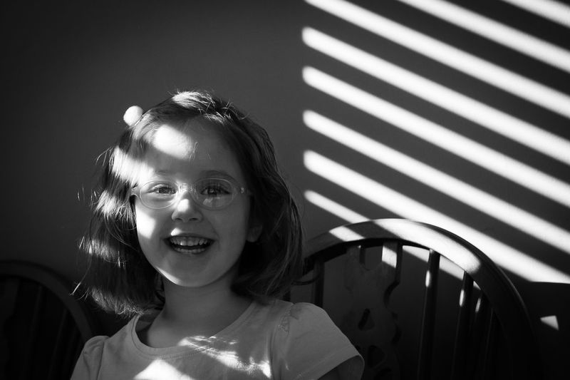 Portrait Smiling Headshot Child Happiness Childhood One Person Girls Looking At Camera Front View Emotion Lifestyles Females Women Real People Casual Clothing Innocence Hairstyle Blackandwhite Black And White Toddler  Shadows & Lights Indoors  Glasses Candid