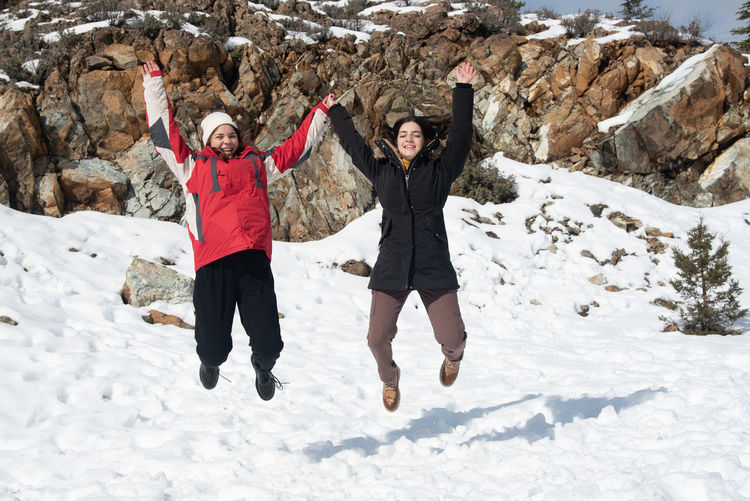Two young happy teenage girls jumping with pleasure at snow.