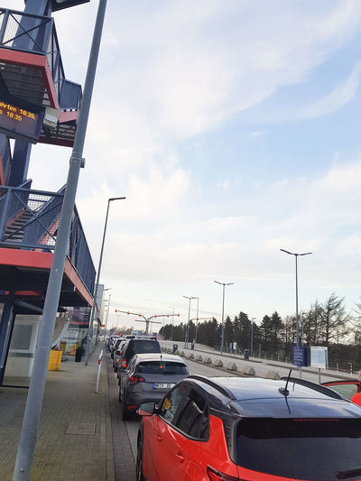 Cars on road against sky in city