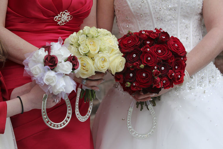 'Bride and bridesmaids flowers' Bouquet Bridal Bouquet Bride Brides Maid Bridesmaid Bouquets Celebration Close-up Floral Life Events Lifestyles Love Lucky Charms Lucky Horseshoes Real People Red Wedding Wedding Ceremony Wedding Day Wedding Dress Wedding Party Women