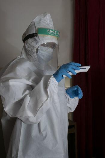 Woman wearing protective suit standing indoors