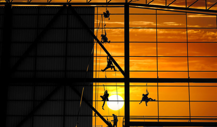 Silhouette of structure for steel wall frame installation by worker team