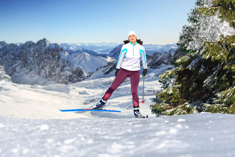 Portrait of woman with ski-wear standing on snow against mountains