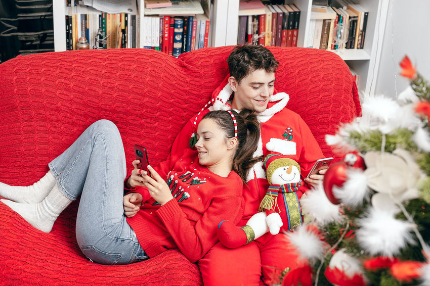Couch Ornament Ornaments One Woman Only One Man Only Young Adult Couple - Relationship People Real People Red Indoors  Interior Home Interior Warm Clothing Young Women Christmas Present Christmas Decoration Women Sitting Females Living Room Tree Christmas Ornament christmas tree Young Couple Romance Romantic Activity Boyfriend Decorating The Christmas Tree Christmas Human Connection