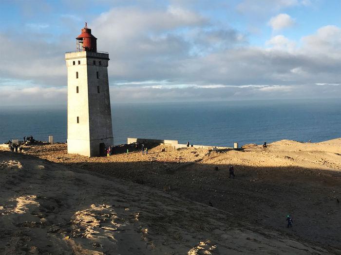 Lighthouse on beach by sea against sky