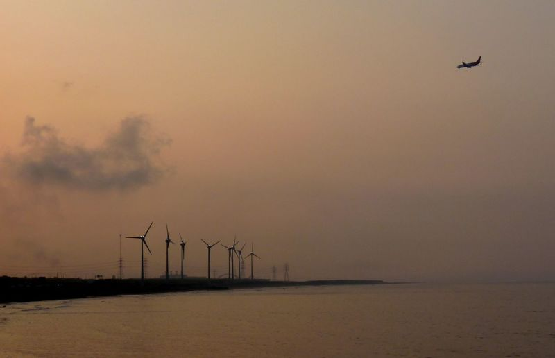 Windmills by sea against sky during sunset