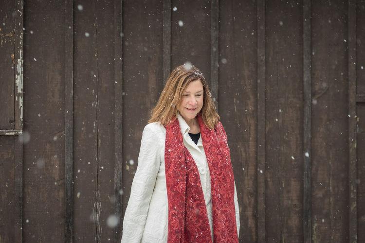 Young woman walking against wall during snowfall