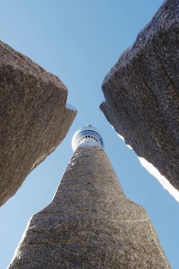 Low angle view of rocks by tokyo sky tree against clear blue sky