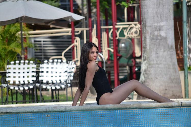 Full length of woman sitting at swimming pool