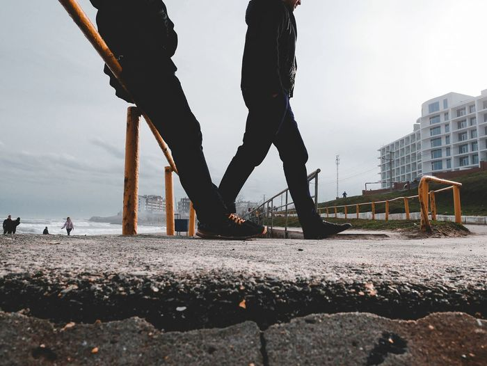 Low section of people walking on road in city