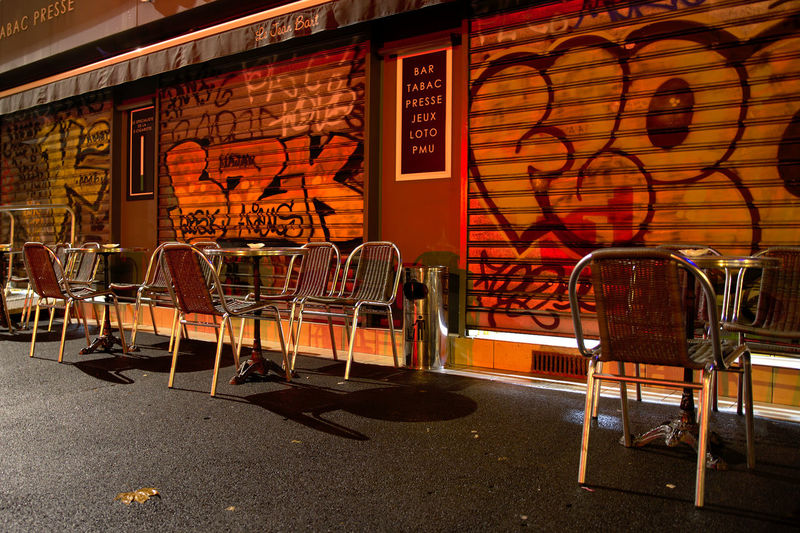 Empty chairs and tables against wall at cafe