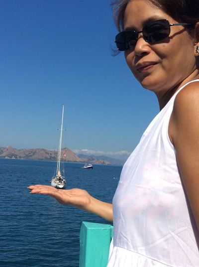 Optical illusion of woman wearing sunglasses holding boat on sea against blue sky