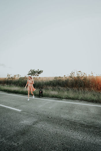 Woman on road amidst field against clear sky