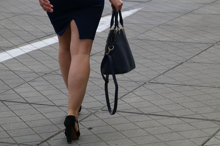 Low section of fashionable woman walking with purse on footpath