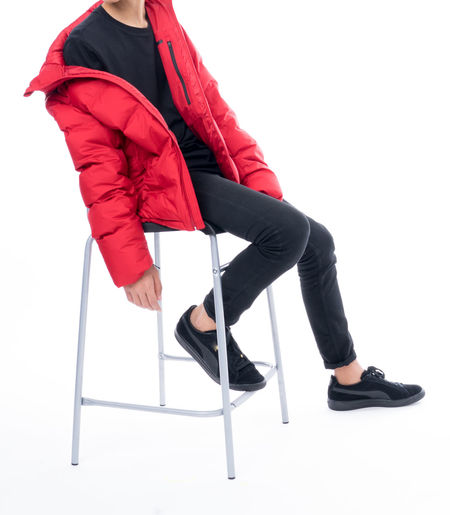 A teenager wearing red jacket , black top and bottom isolated on white Black Shoes!!  Winter Coat Black Shoes Casual Clothing Chair Cut Out Day Fashion Fashion Model Full Length Guy Jacket Legs Apart Low Section One Person People Real People Shoe Sitting Studio Shot White Background Young Adult