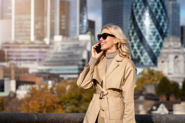Young woman wearing long coat talking on phone while standing outdoors